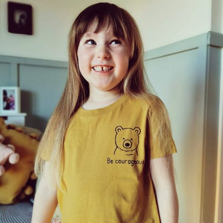 Girl with long hair wears Yellow Be Courageous Christian T-Shirt for Kids by Ellen Hopkin Creates at Cheerfully Given