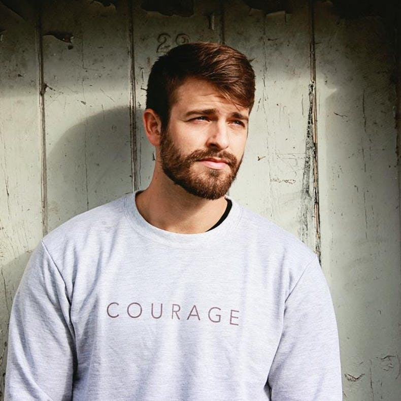 Man stands against wall in grey courage sweatshirt at Cheerfully Given
