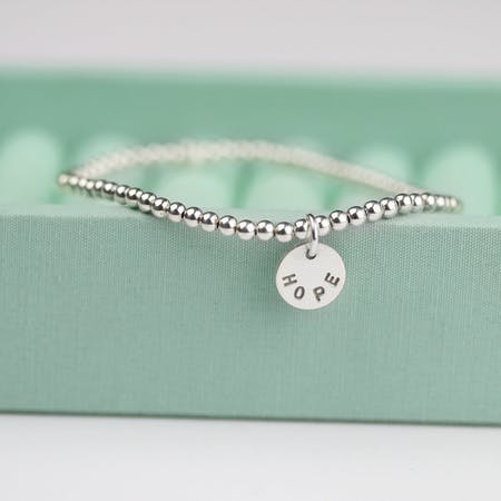 Hope silver bead bracelet hangs on edge of pale green jewellery box | Jordan Lily Designs at Cheerfully Given