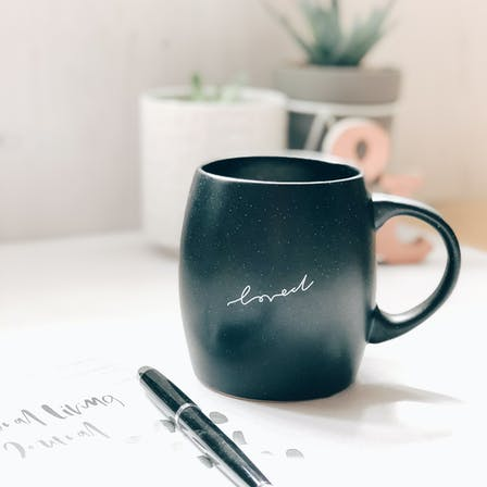 Large black mug with word loved handlettered on the front sitting on a desk | Hope and Ginger | Cheerfully Given