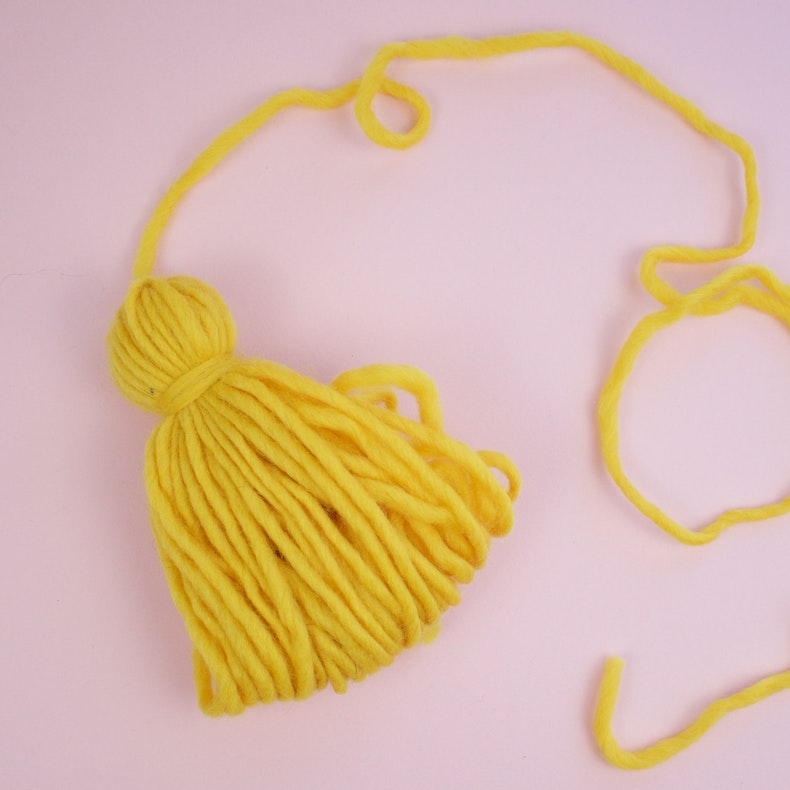A completed yellow tassel lies on a pink backdrop at Cheerfully Given