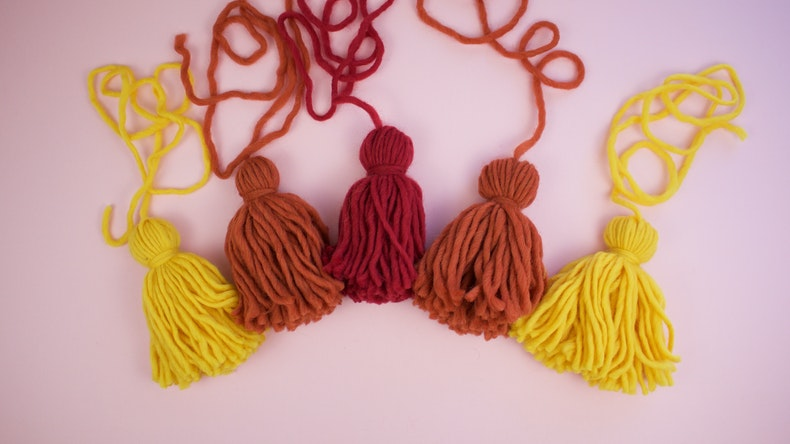 Five fire coloured tassels lying on a pink backdrop as part of the Pentecost wall hanging at Cheerfully Given