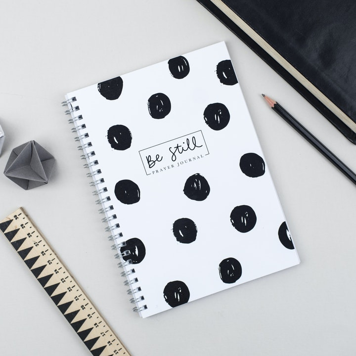 Be Still Prayer Journal has a white cover with black spots on it - by Ali Marriott