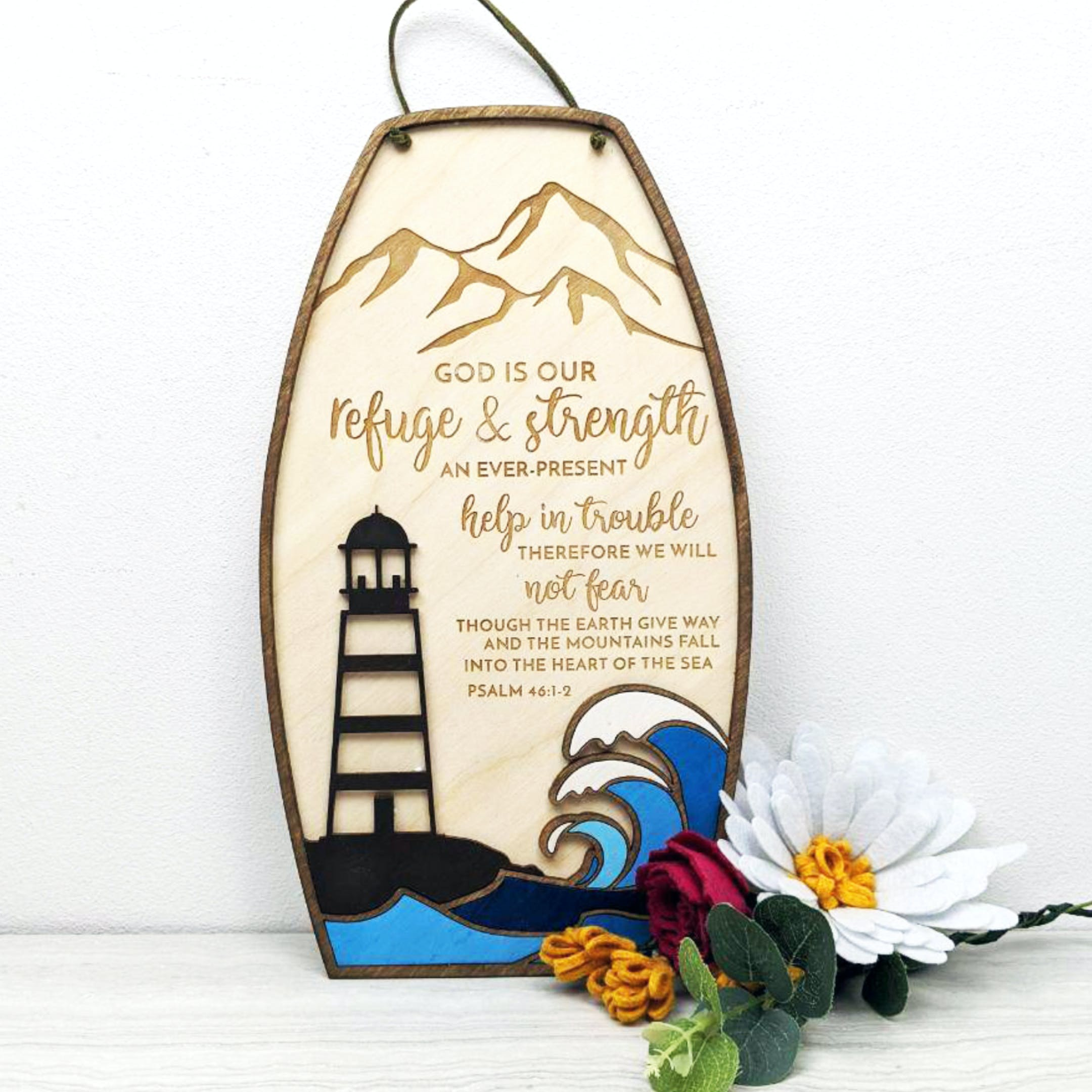 A wooden sign with a lighthouse on one side and Psalm 46 the other with burnt work mountains at the top by Birch and Tides