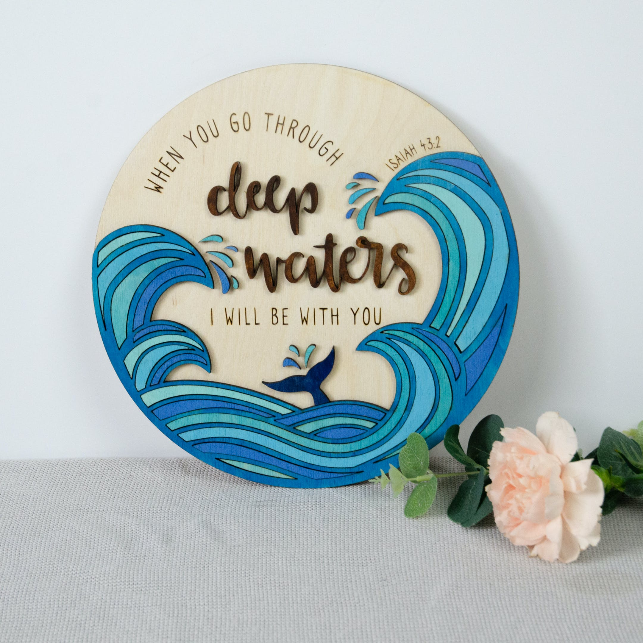 Round wooden sign with blue waves around the bottom and words Deep Waters highlighted in the centre by Birch and Tides
