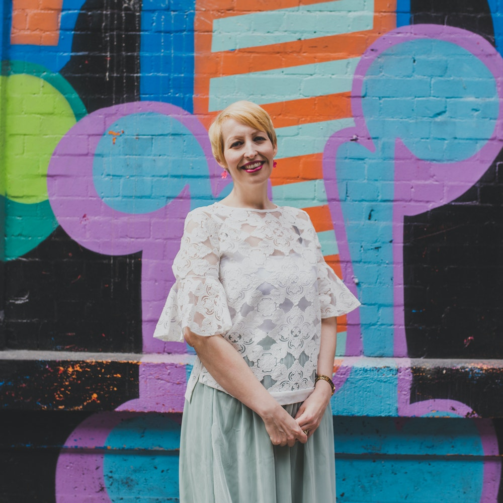 Kate Dugmore of Bloom Jewellery standing beside a graffiti art wall | Cheerfully Given