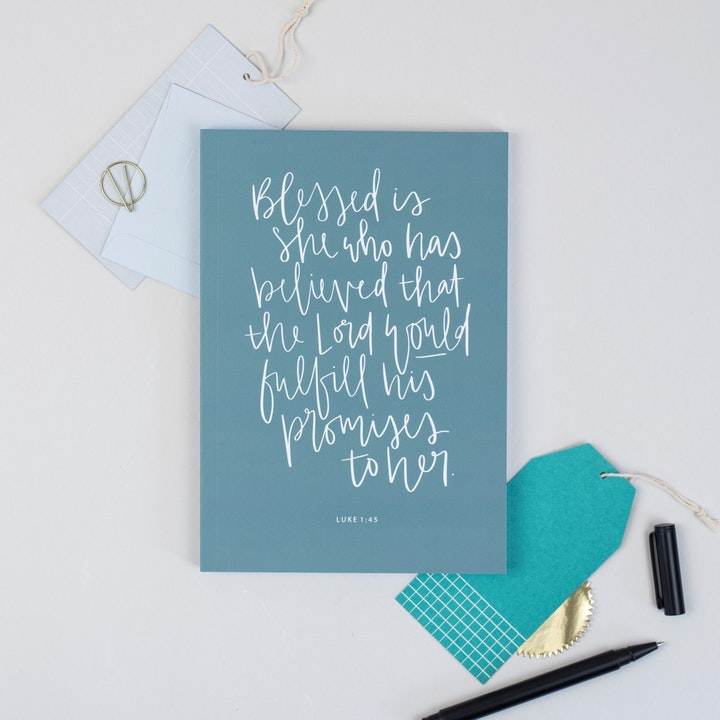 Deep teal devotional journal with white handlettered Bible verse of Luke 1:45 by Hope and Ginger | Cheerfully Given