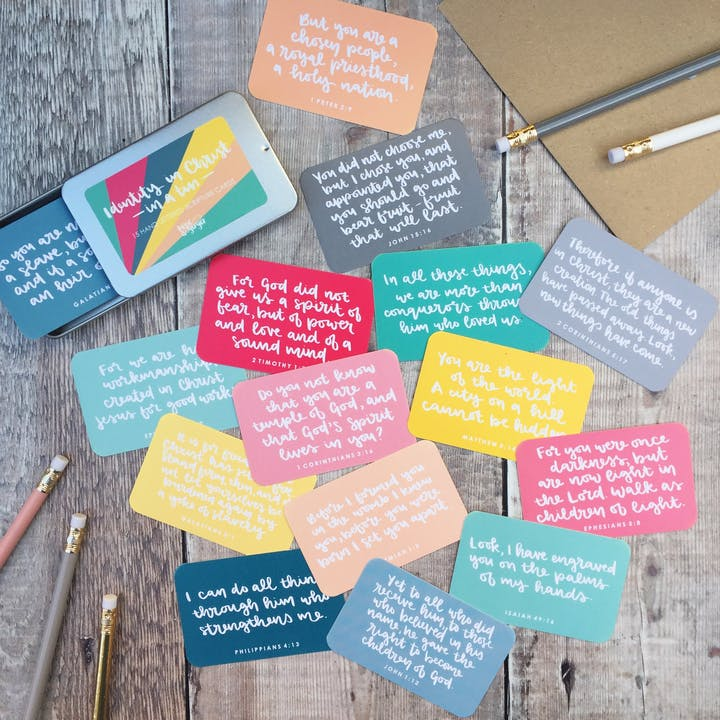 Set of 15 brightly coloured Scripture cards (business card size) and a metal tin on a wooden desk by Hope and Ginger @ Cheerfully Given