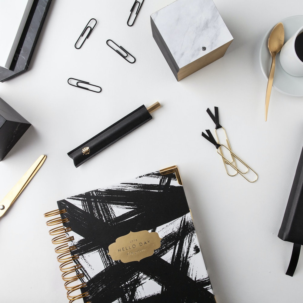 Black white and gold Hello Day Planner lies on monochrome desk