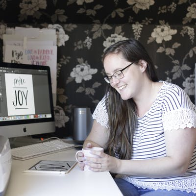 Heather Kauffman sits at a desk with a cup of tea, owner of HK Creations, Bible Journaling Supplies for the UK