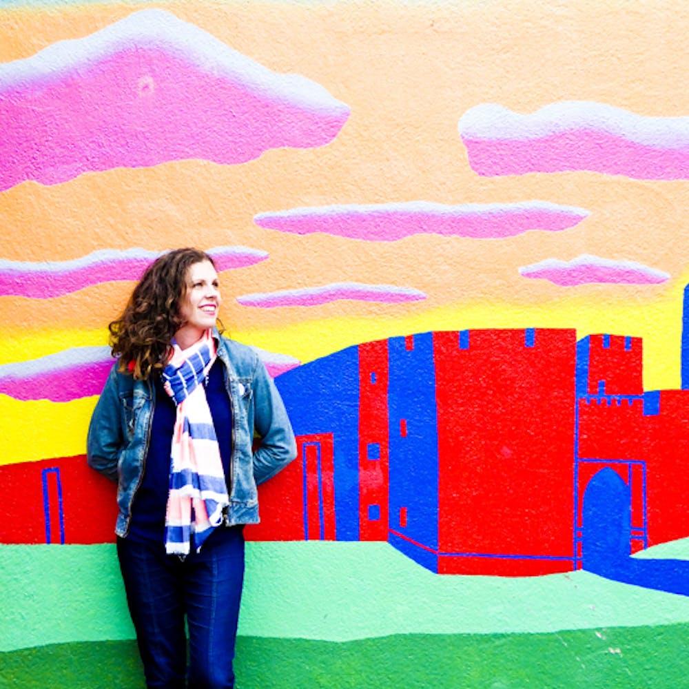 Headshot of Judy Bainbridge standing next to graffiti art wall at Cheerfully Given