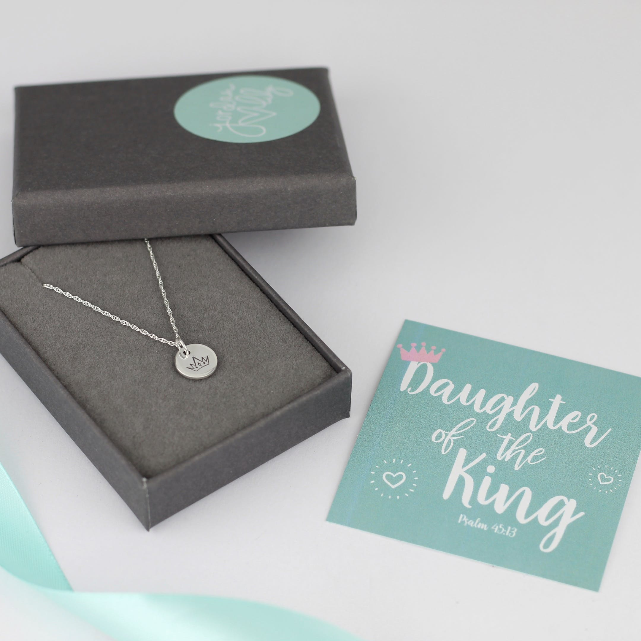 Grey box holding silver necklace with silver disc pendant stamped with crown and a teal card saying Daughter of the King by Jordan Lily Designs