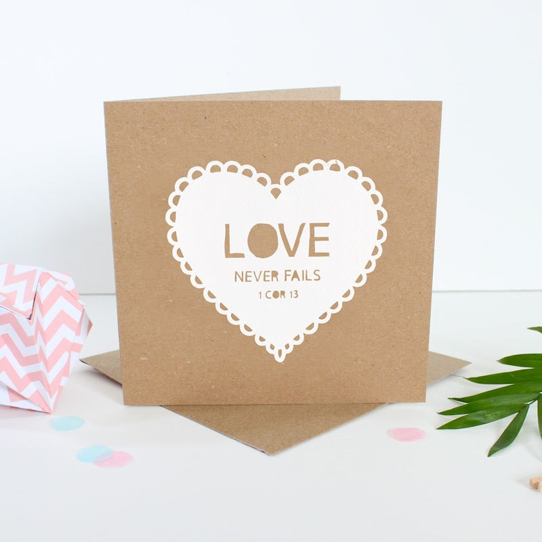 Brown kraft card with white paper cut out heart with words Love never fails by Kiwi Tree Designs | Cheerfully Given