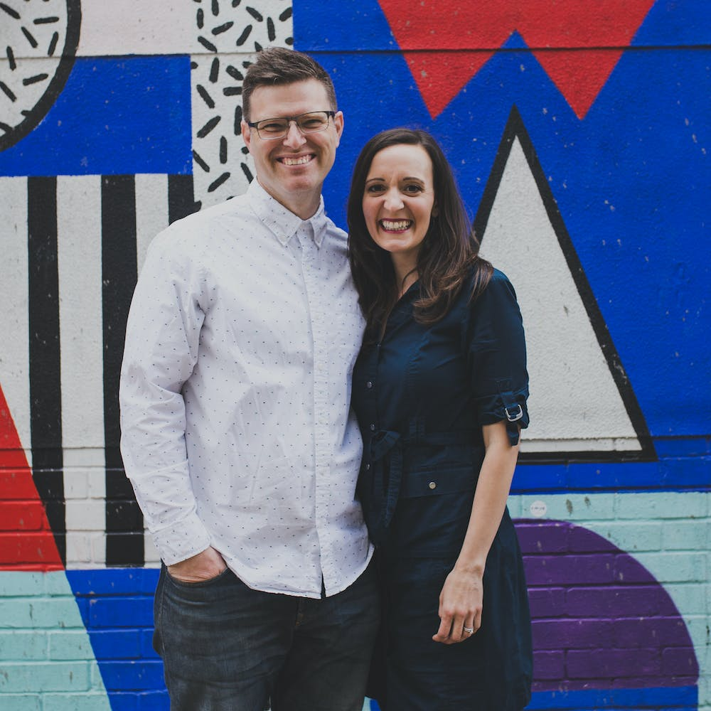 Maya & Patrick Laurent of Laurent Collective stand smiling before a graffiti art decorated wall | Cheerfully Given