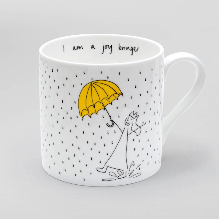 White mug with girl in rain & umbrella and words I am a joy bringer by I Am So Many Things | Cheerfully Given