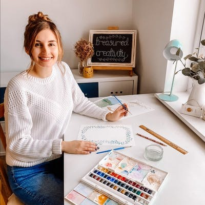Beth George sits at her desk with watercolour palette and paper, creator of Treasured Creativity   Cheerfully Given