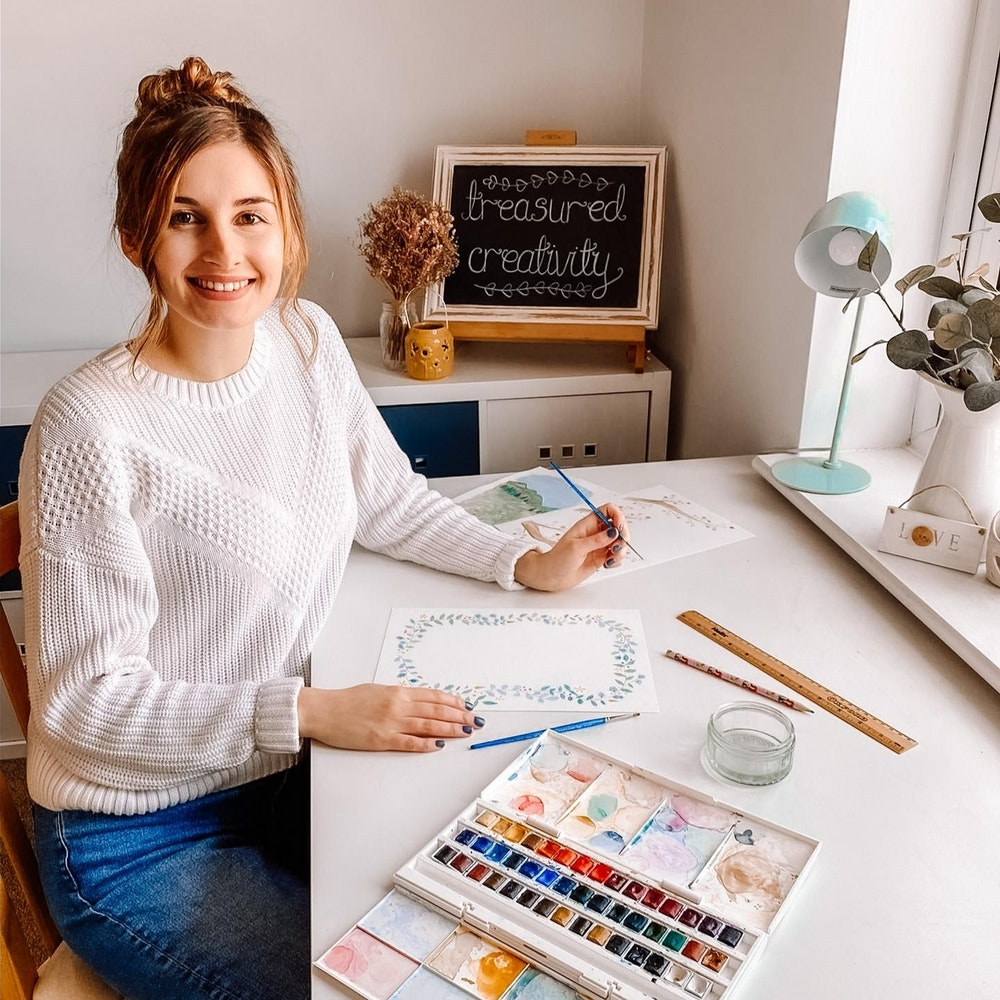 Beth George sits at her desk with watercolour palette and paper, creator of Treasured Creativity | Cheerfully Given