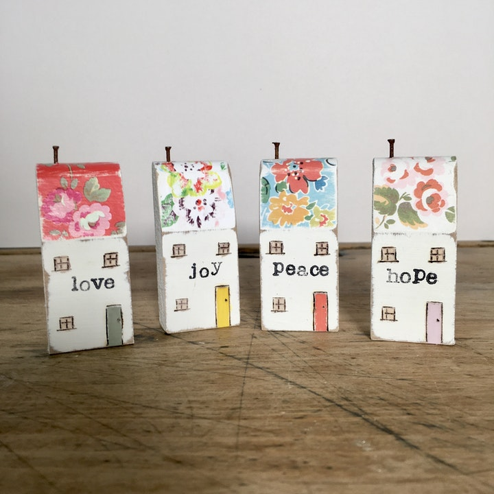 Four wooden houses with love joy peace hope on wooden shelf as Christian home decor this spring by The Pip House at Cheerfully Given