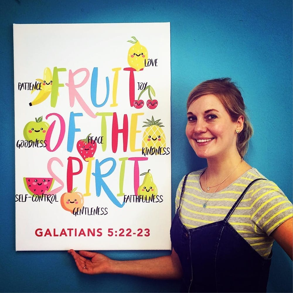 Zunelle of Nova Grace stands with her Fruit of the Spirit poster against a blue backdrop | Cheerfully Given